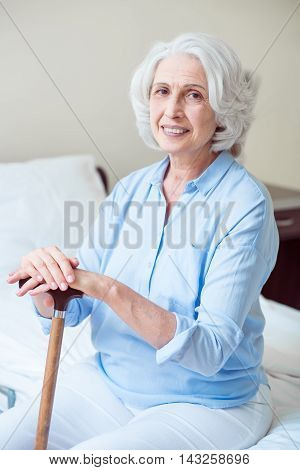 Be happy. Smiling and happy senior woman being at hospital ward holding crutch