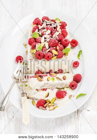 Homemade semifreddo with pistachio and raspberry in oval dish over old white painted wooden background, selective focus, horizontal composition