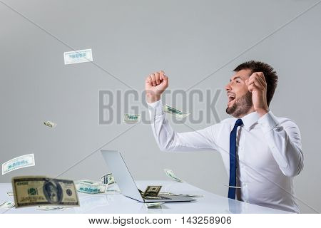 the young man behind the laptop. It uses a computer while sitting at a table. enjoys hands up. Office clothing. the top falling money, dollars