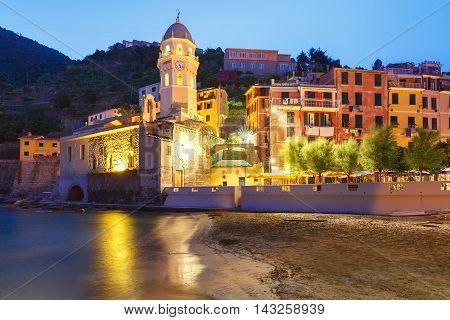 Night fishing village Vernazza with Santa Margherita di Antiochia Church, Five lands, Cinque Terre National Park, Liguria, Italy.