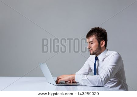 young man smiling at the camera uses a laptop computer while sitting at a table. Office clothing. copyspace