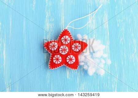 Stuff the felt Christmas star with hollowfiber. Christmas sewing craft. Red hanging star ornament decorated with white balls on a blue background. How to teach a child to sew. Tutorial. Step. Top view