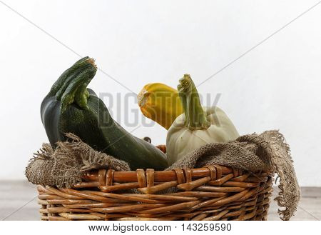 Fresh zucchini or marrow squash or courgette in basket on burlap against wooden background. Vegetables in different shapes and colors concept of diversity horizontal view