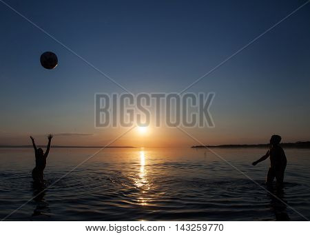 Photo children playing ball in the water at sunset.