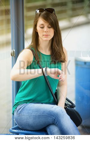 young brunette woman sitting at bus stop and looking at her wtach