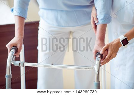 Medical service. Cropped image of professional doctor helping senior woman with walking frame