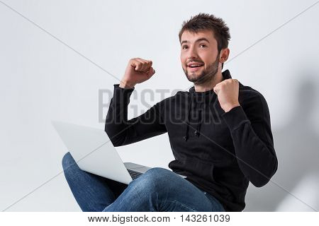 a young man in casual clothes working on a laptop. glad hands up