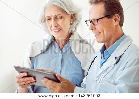 Modern doctor. Delighted and content doctor holding digital tablet and positive old female patient standing near him
