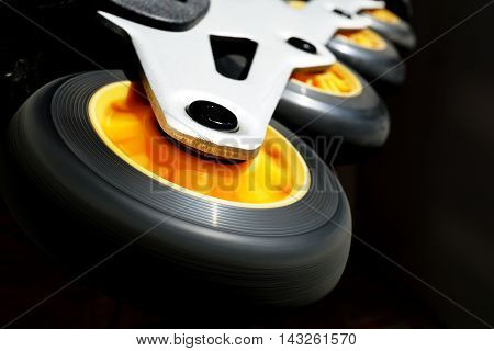 Detail of a black and yellow roller skates (in-line skates) in the darkness as a symbol of movement and speed