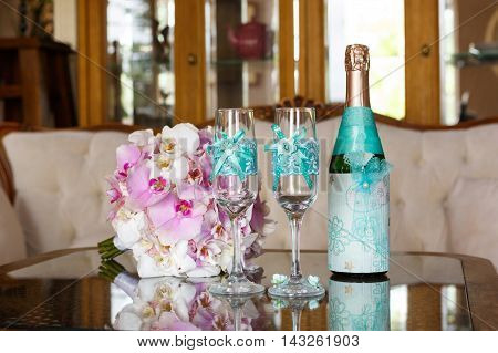 Wedding still life. Two decorated glasses a bottle of champagne and bride's bouquet of orchids