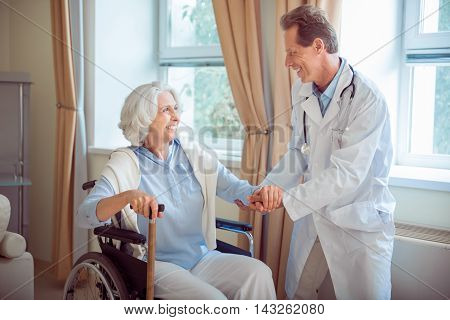 In clinic. Cheerful doctor helping and supporting positive senior patient in wheelchair