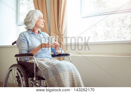 Alone. Sad and depressed old woman in wheelchair with cup of tea