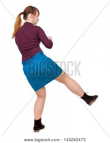skinny woman funny fights waving his arms and legs. Isolated over white background. The red-haired girl in a blue skirt leg beats.