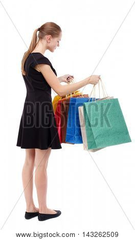 back view of woman with shopping bags. backside view of person.  Rear view people collection. Isolated over white background. Blonde in a short black dress looks into colorful shopping bags.