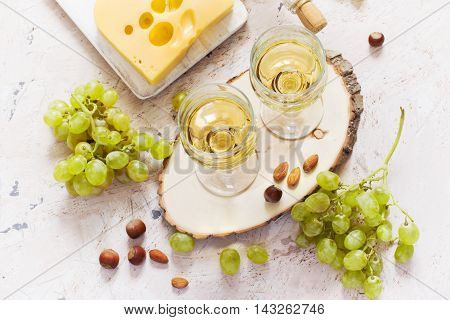 Glasses of white wine grapes nuts and cheese on white background