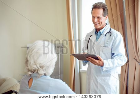 Consultation. Back of senior woman and smiling doctor standing and holding digital tablet