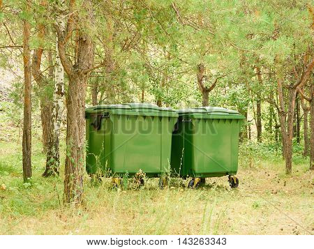 Two large green garbage container outdoors in a park.