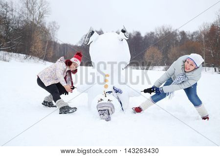 Upside down snowman and two women try to raise it at winter day