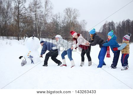 Six people play - try to raise upside down big snowman at winter day