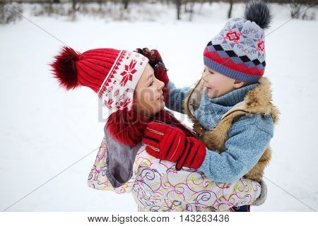 Woman embraces her little handsome son at winter day in park