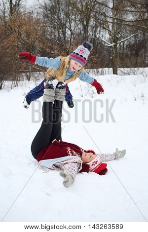 Happy woman lies on her back and holds little son on feet in snow