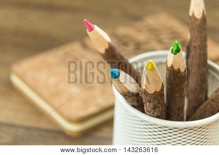 colored natural wooden pencils in metal office pencil holder