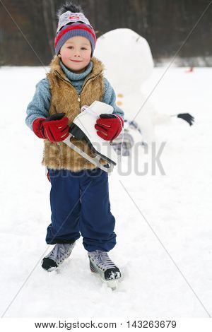 Little handsome boy with skate stands near upside down snowman at winter day