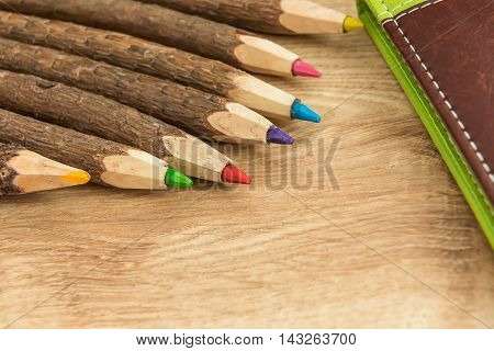 wood colored natural pencils and leather notebook on the desk