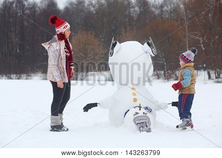 Little boy and woman stand near upside down snowman at winter day