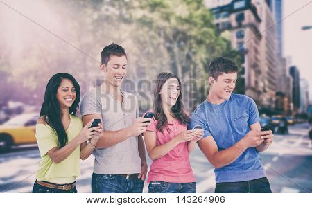 Four laughing friends sending texts on their phones against new York street