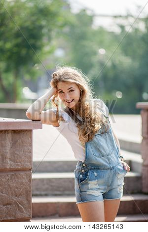 girl stands leaning against a wall at her