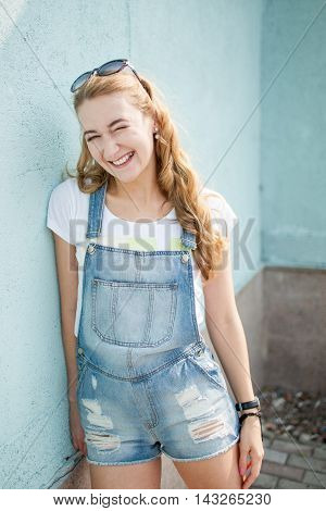 girl against a wall looking away and smiling