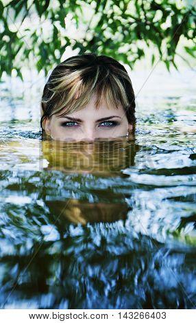Young beautiful girl in a dark river water.