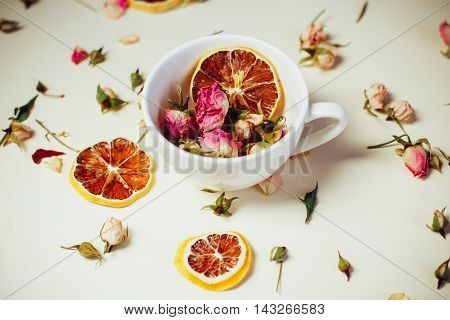 Dried Flowers Dried Roses And Round Slices Of Lemon Laid On A White Background And The White Cup