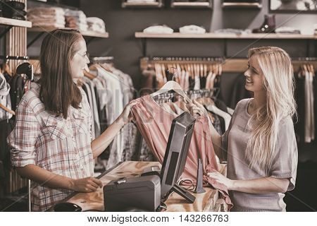 Smiling blonde doing shopping in clothes store