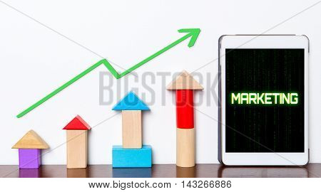 Marketing strategy growing concept on tablet. Toy block rise with Marketing success diagram graph. Tablet with hi tech tech text Marketing success rising up.