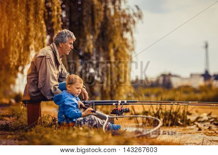 Grandfather with a grandson on fishing on the lake
