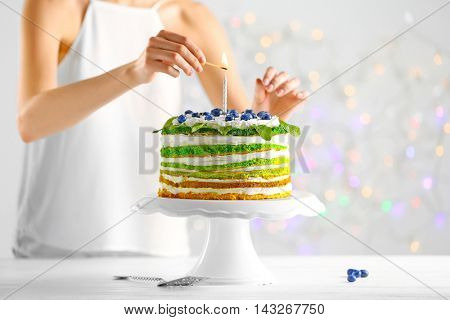 Woman decorating delicious cake on light background