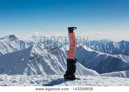 Girl in warm clothing standing on his head on the white snow in the mountains