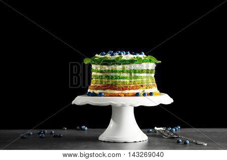 Delicious cake on stand on dark background
