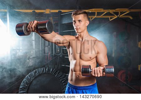Muscular man doing heavy weight exercise for biceps with dumbbells in modern gym