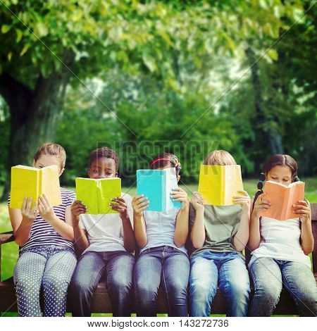 Children reading books at park against trees growing on grassy field