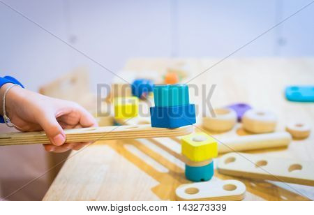 Child hand is building a colorful wooden block engineering toy.