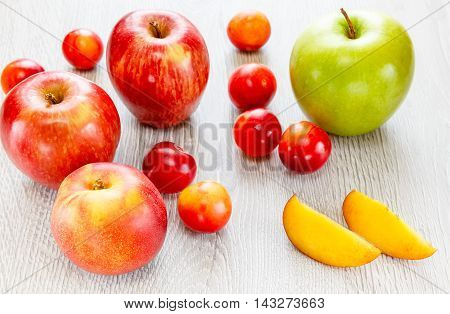 Apples nectarines plums on a wooden background