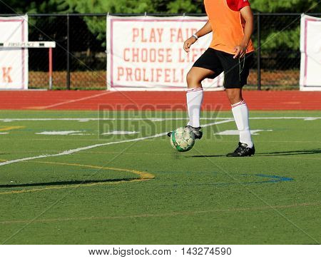 Soccer player trapping soccer ball on a turf field