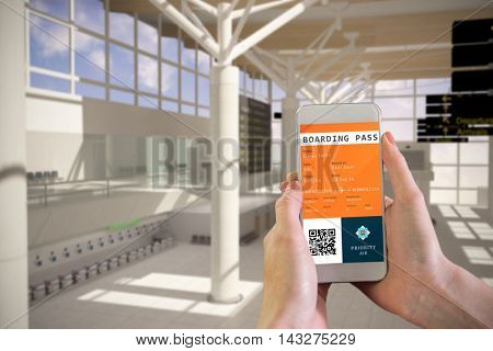Hand holding smartphone against digital composite image of airport