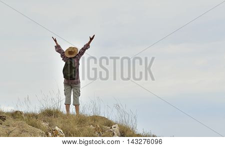 Woman with hands up standing on the top of the mountain