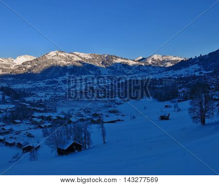 Sunrise on a beautiful winter morning in Gstaad. Famous village and travel destination in the Swiss Alps.