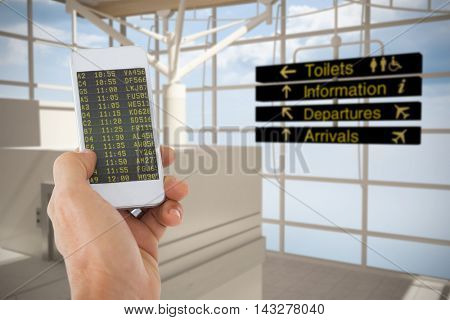 Male hand holding a smartphone against black airport departures board for australia