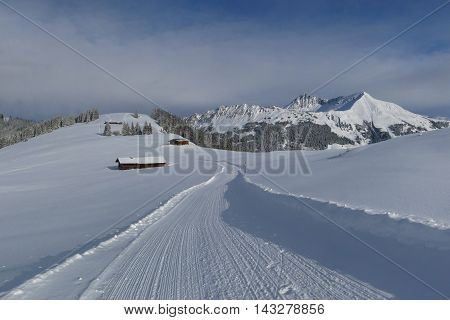 Snow covered mountains in Gstaad and winter hiking path on Mt Wilspile.